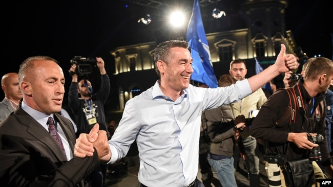 "Ramush Haradinaj (left), leader of the Alliance for the Future of Kosovo (AAK), and Kadri Veseli (center), leader of the Democratic Party of Kosovo (PDK), of the ""war wing"" coalition celebrate their victory in Pristina on June 11."