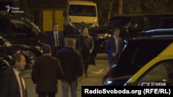 Охоронець веде жінку до автівки, зареєстровану на ГПУ