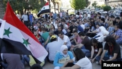 Syrian youths attend a sit-in in Damascus on June 29 to honor victims of the recent violence.