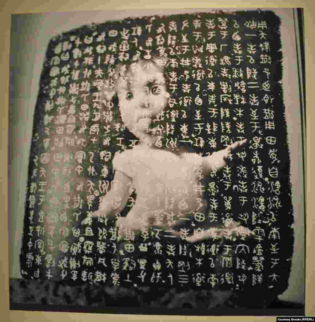A doll is trapped beneath a stone inscribed with Chinese characters.