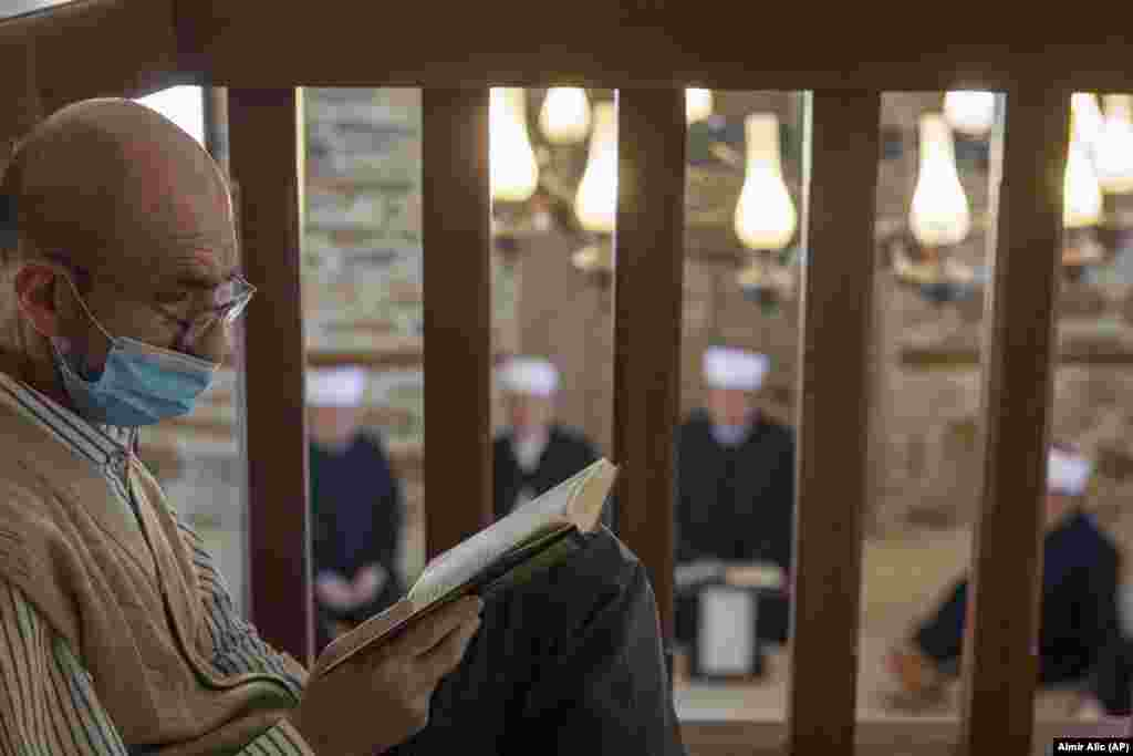 A man reads the Koran as imams attend the Ramadan prayer in a mosque without worshippers in Zenica, central Bosnia, on April 23.