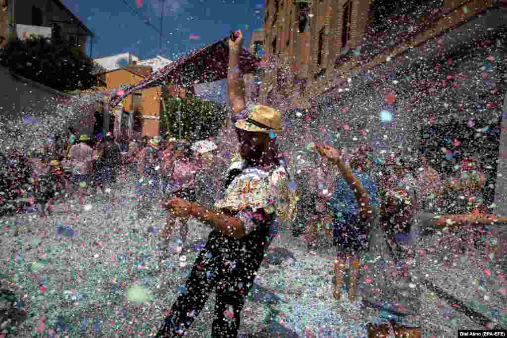 People are showered with confetti during a traditional holy procession in the Spanish village of Betera on August 15. (epa-EFE/Biel Alino)