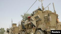 An Iraqi soldier patrols near U.S. military armoured vehicles as the U.S. Army prepares to leave a military base in Mahmudiyah in July.