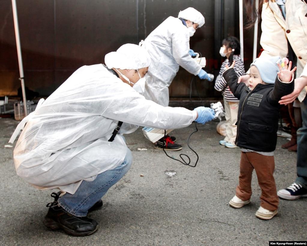 Перевірка на наявність радіоактивного забруднення в дітей, які приїхали в місто Коріяму з району евакуації біля АЕС «Фукусіма-2», що за 12 кілометрів на південь від першої, 13 березня 2011 року. Ця станція теж зазнала значної шкоди і відтоді так і не поновила роботу, але на ній катастрофи вдалося уникнути
