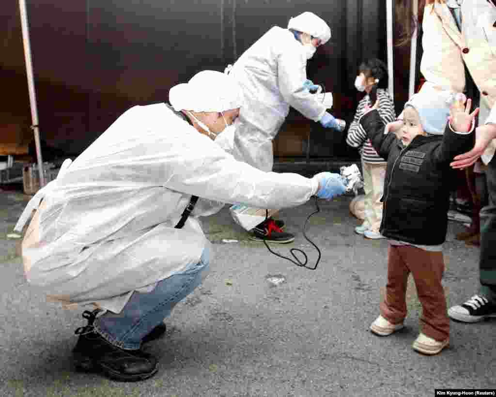 """Понимая, что процесс разрушения залитой цунами АЭС """"Фукусима-1"""" принимает необратимый характер, власти начали вывозить население близлежащих деревень. Проверка на радиацию детей, эвакуированных из районов, прилегающих к станции, в город Корияма 13 марта 2011 года"""