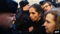 Полицейлер Pussy Riot панк-тобының мүшелері Надежда Толоконникова мен Мария Алехинаны сот ғимараты маңында тоқтатып тұр. Мәскеу, 21 ақпан 2014 жыл.