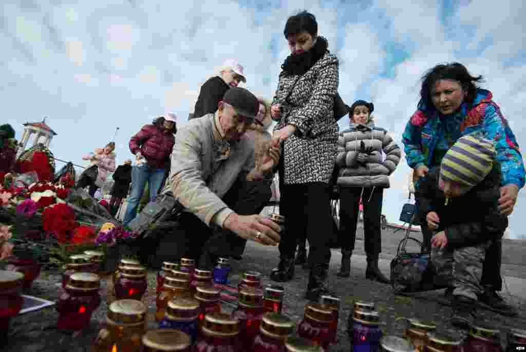 Residents of Sochi place candles and lay flowers  at an impromptu shrine paying tribute to the victims of a plane that crashed minutes after taking off from the Black Sea city on December 25, killing all 92 people on board. (epa/Yevgeny Reutov)