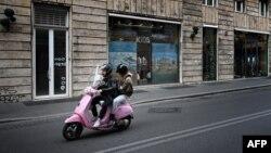 Люди на мотороллере на улице в столице Италии. Рим, 12 мая 2020 года.
