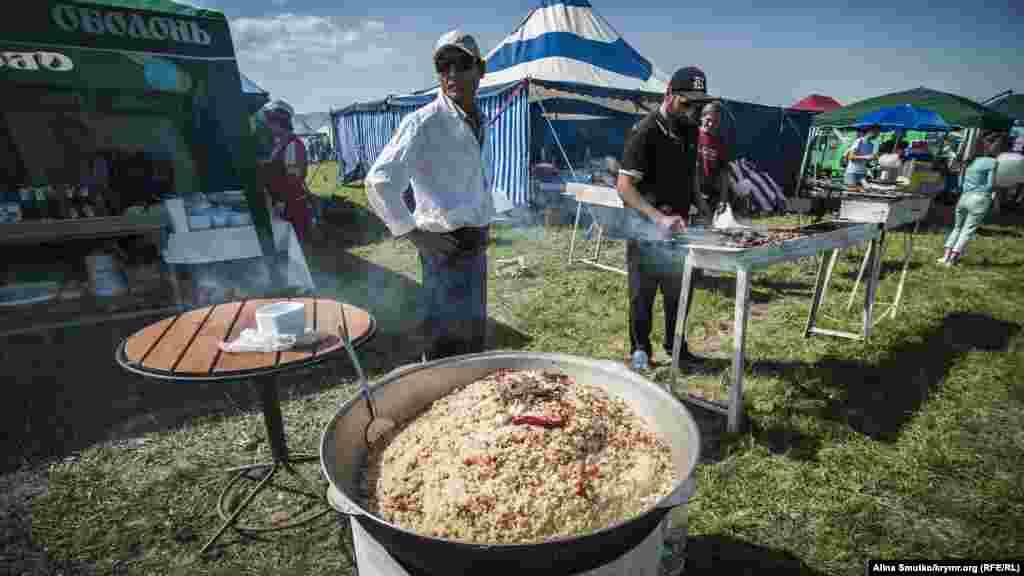 Мужчина готовит плов и шашлыки