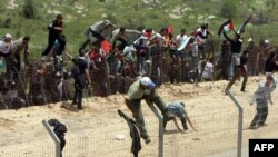 Участники беспорядков на Голанских высотах перелезают через заграждение на границе с Израилем. 15 мая 2011 года.