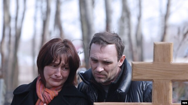 The parents of Maksim Mareyev, who was killed by one of the bombings in Moscow's subway on March 29, mourn at his funeral on March 31.