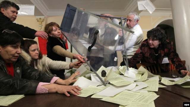 Members of a local electoral commission empty a ballot box for counting at a polling station in Sevastopol, in Crimea, Ukraine, on March 16.