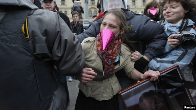 Russian police detain an opposition activist holding a portrait of President Vladimir Putin during a protest on Putin's birthday in Moscow on October 7.