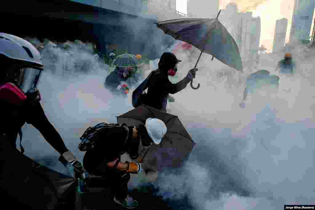Anti-government protesters protect themselves with umbrellas from tear gas during a demonstration near government buildings in Hong Kong on September 15, 2019. (Reuters/Jorge Silva)