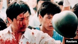 A blood-covered protester holds a Chinese soldier's helmet following violent clashes with military forces during the 1989 pro-democracy demonstrations in Beijing's Tiananmen Square in this June 4, 1989, photo.
