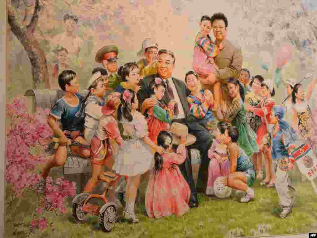 "A painting featuring North Korean leaders Kim Il Sung (seated) and Kim Jong Il is on display during the opening of of Democratic People's Republic of North Korea state art exhibition ""Flowers of Kim Il Sung"" in Vienna in May 2010."