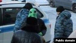 """Қоғамдық белсенді Махамбет Әбжан (ортада, жасыл маска киінген) """"Қазғарыш"""" агенттігі алдындағы акция кезінде. Астана, 27 қаңтар 2014 жыл. Махамбет Әбжанның Фейсбук парақшасынан алынған сурет."""