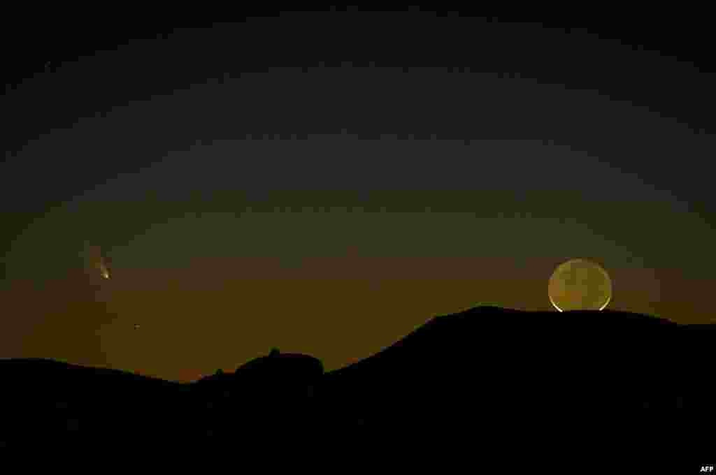 The comet PanSTARRS (left) is seen with a crescent moon as both set over the Very Large Array radio telescope antenna near Magdalena, New Mexico. The comet, now just faintly visible in the Northern Hemisphere, was discovered in June 2011 by the Panoramic Survey Telescope and Rapid Response System (PanSTARRS) in Hawaii. (AFP/Stan Honda)