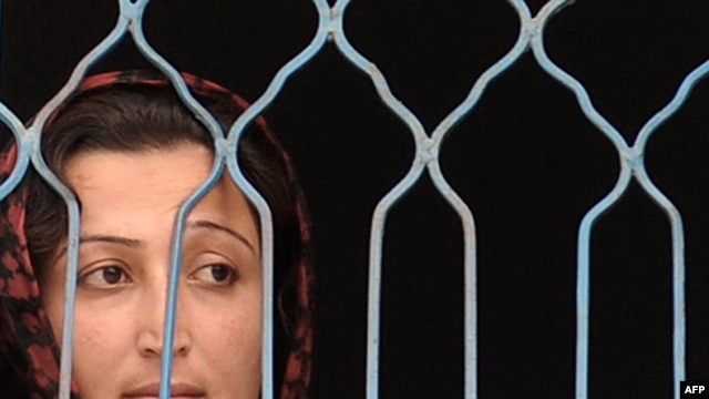 A prisoner looks out from a fenced window at the Female Detention Center in Kabul.