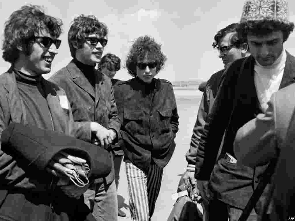 Dylan arrives at Le Bourget airport in France on May 22, 1966, surrounded by his band.