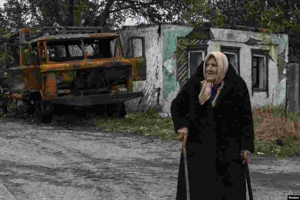 A woman walks along a road past a burnt-out vehicle in the town of Ilovaysk in eastern Ukraine, on September 25. (Reuters/Marko Djurica)