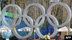 Workers put the finishing touches on Olympic rings at Medals Plaza in Whistler, Canada.
