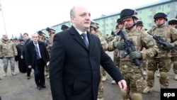 Georgian Fefense Minister Mindia Janelidze (C) inspects Georgian soldiers during a farewell ceremony marking their departure to Afghanistan, at the military base of Vaziani outside Tbilisi on December 16, 2014.