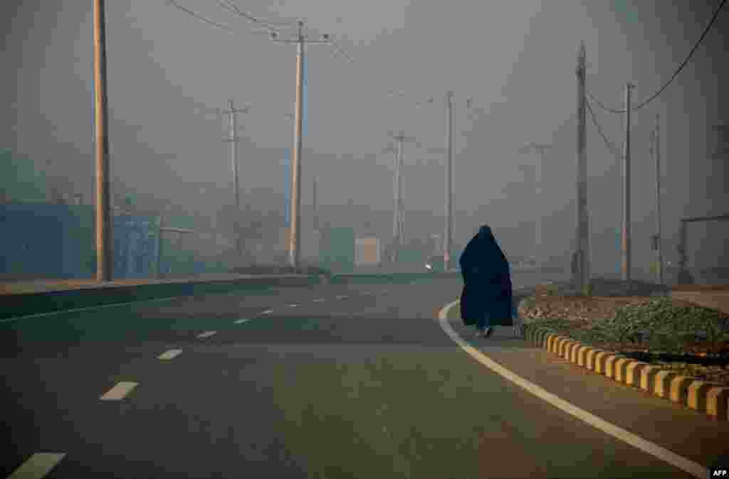 An Afghan burqa-clad woman walks along a road in Mazar-e Sharif. (AFP/Farshad Usyan)