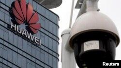 O cameră de supraveghere în fața logo-ului Huawei, la fabrica din Dongguan, provincia chineză Guangdong.