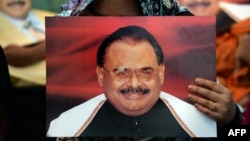 Supporters of Pakistan's Muttahida Qaumi Movement (MQM)party hold photographs of party leader Altaf Hussain during a June protest in Karachi.