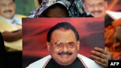 Supporters of Pakistan's Muttahida Qaumi Movement (MQM) party hold photographs of party leader Altaf Hussain as they stage a sit-in calling for his release in Karachi on June 3.