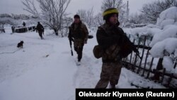Ukrainian soldiers patrol an area in the government-held village of Travneve on November 23.