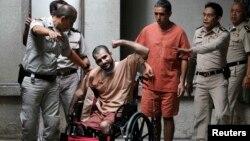 سعید مرادی در پی انفجار یکی از بمبهایی که آن را حمل میکرده، هر دو پای خود را از دست داده است. در تصویر محمد خزایی، متهم ردیف دوم، نیز کنار او ایستاده است.
