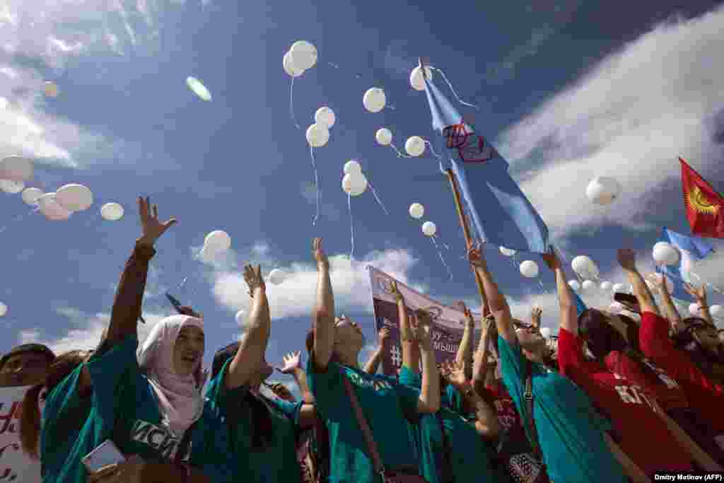 Kyrgyz students release white balloons as they protest against bride kidnapping in Bishkek after a 20-year-old woman was murdered in a police station by her kidnapper. (AFP/Dmitry Motinov)