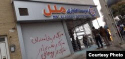 "A damaged credit union branch in Shiraz, Iran. Slogan says, ""Death to Khamenei"", ""Death to Rouhani""."