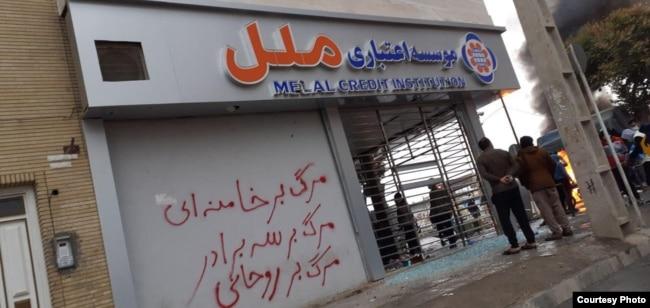 "A damaged credit union branch in Shiraz, Iran. Slogan says, ""Death to Khamenei"", ""Death to Rouhani""."