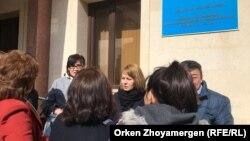 Журналист Светлана Глушкова (ортада) cот ғимараты қасында тұр. Нұр-Сұлтан. 1 сәуір, 2019 жыл