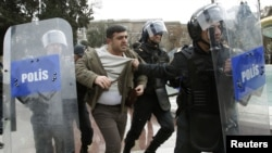 Azerbaijan -- Police officers detain one of the opposition activists during an unauthorized rally in central Baku, 26Jan2013