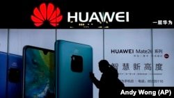 CHINA - A woman browses her smartphone as she walks by a Huawei store at a shopping mall in Beijing, December 11, 2018.