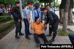 A man sits on the ground as police move to detain him on Almaty's Astana Square. June 10, 2019