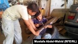 طفلان يعملان في ورشة لتصليح السيارات في كربلاء