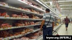 Симферопольдегі Auchan супермаркетінде тауарларға қарап тұрған азамат. Қырым,15 қыркүйек 2015 жыл.