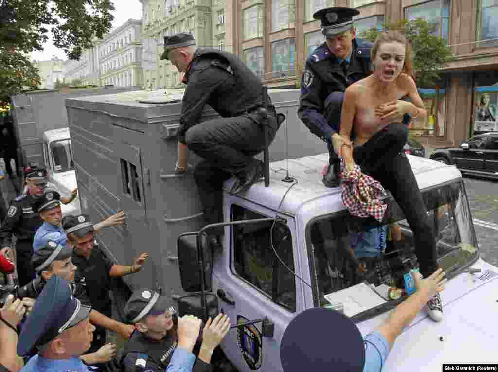 Поліцейські затримують Оксану Шачко на даху поліцейської автівки для перевезення затриманих під час мітингу біля одного з київських судів. Femen виступили проти переслідування, як вони стверджували, прем'єр-міністра України Юлії Тимошенко. 2011 рік