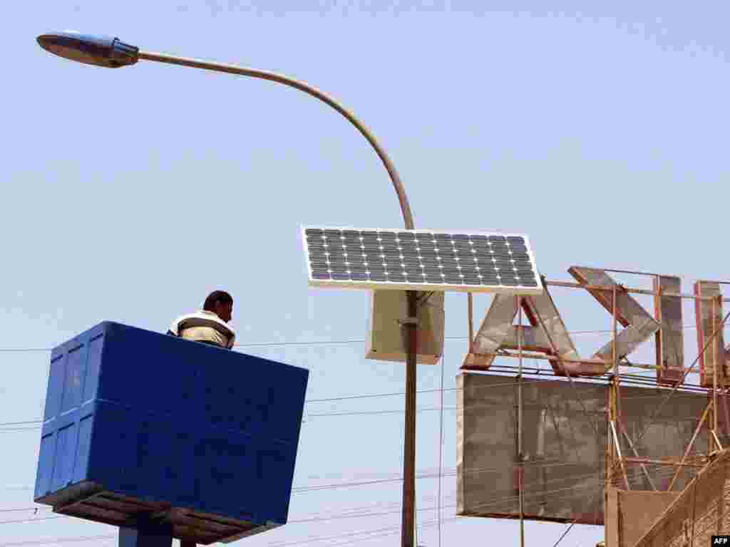 Iraq -- A municipal worker is lowered after adjusting a solar panel attached to the top of an electricity pylon along the central isle of a main road in the Karada district of Baghdad, 24May2008 - IRAQ, Baghdad : A municipal worker is lowered after adjusting a solar panel attached to the top of an electricity pylon along the central isle of a main road in the Karada district of Baghdad on May 24 2008.The solar panel which are made in China are set to fill sun power during day light hours and run the streets lights at night. The Ministry of Electricity plans on using solar power to light the main Baghdad ring road and airport highway at night. AFP PHOTO / SABAH ARAR green03 Replacing fossil fuels with renewable energy for electricity