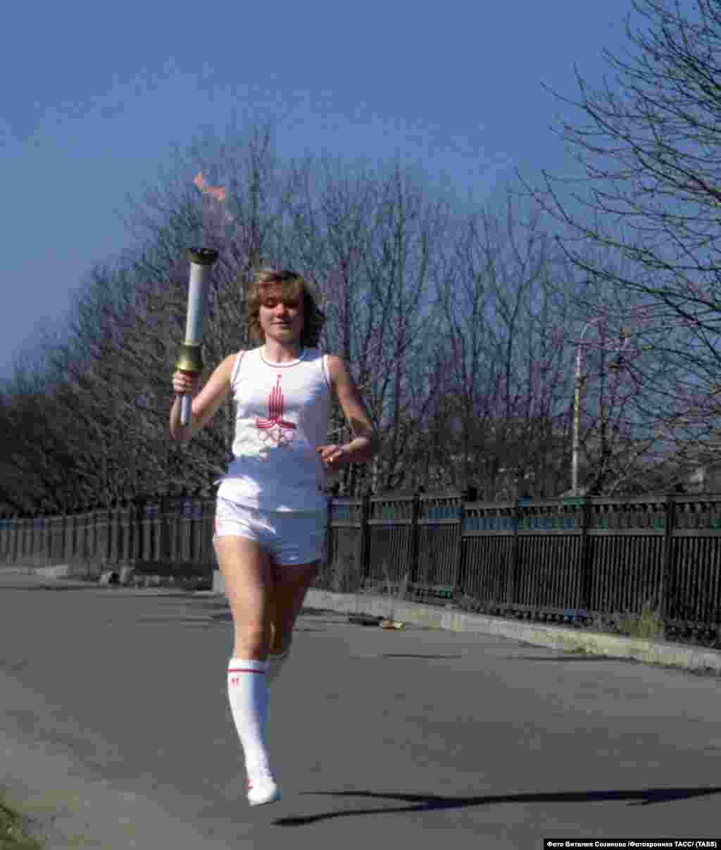 Спортистка со олимписки факел пред отворањето на Игрите.