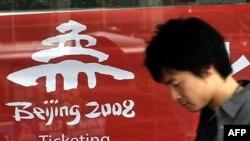 Пекиндегі 2008 жылғы Жазғы олимпиада ойындарына билет жарнамасының жанынан өтіп бара жатқан адам. Пекин, Қытай. 15 сәуір, 2007 жыл.