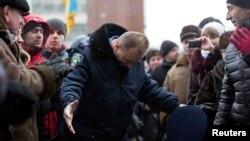 Міліціонер вклоняється мітингувальникам, залишаючи будівлю ОДА в Івано-Франківську, 24 січня 2014 року