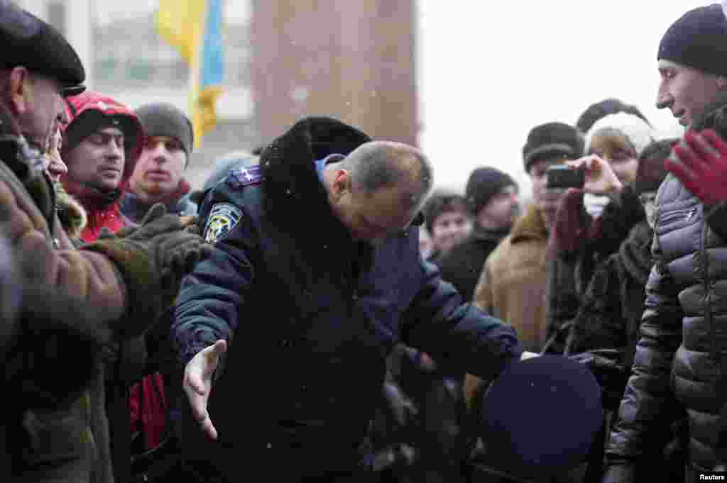 In the town of Ivano-Frankivsk, a police officer bows his head as he leaves the regional administration headquarters, which protesters attempted to take over.