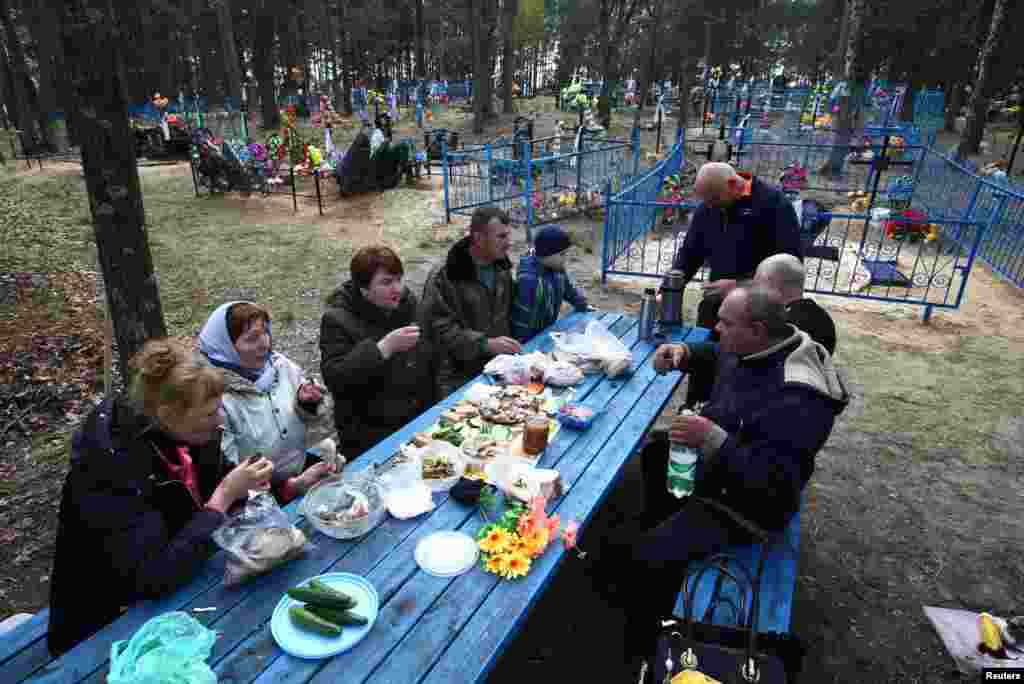 People drink and eat at a cemetery in the abandoned village of Lomysh, near the exclusion zone around the Chernobyl nuclear reactor in Belarus, on the eve of Radunitsa, or the Day of Rejoicing, a holiday in the Eastern Orthodox Church to remember the dead. Every year, residents who left their villages after the Chernobyl blast gather at cemeteries for a day to visit their relatives' graves and to meet with former friends and neighbors. (Reuters/Vasily Fedosenko)