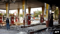 Iran -- An Iranian man checks a scorched gas station that was set ablaze by protesters during a demonstration against a rise in gasoline prices in Eslamshahr, near the Iranian capital of Tehran, on November 17, 2019. - President Hassan Rouhani warned tha